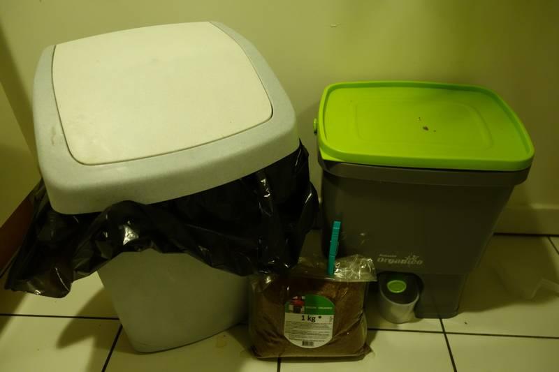 Seau Bokashi (à droite) à côté d'un poubelle ordinaire. Le sachet devant contient le son EM que l'on saupoudre sur les déchets (une petite quantité suffit).